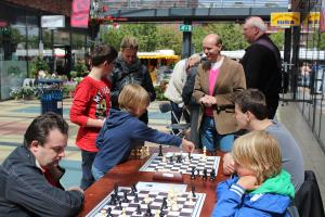 Gezelligheid aan de snelschaaktafels. Ton Mackaaij overziet hoe Guus van Eeden op het punt staat om na te gaan denken over wat te doen op Lg4 (of wordt die loper daar juist net weggehaald?).
